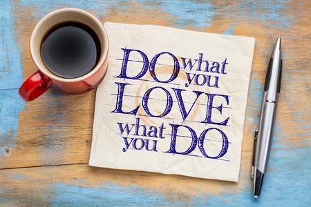 adorar: Faça o que você ama, ame o que você faz - abstrato inspirador da palavra em um guardanapo com chávena de café