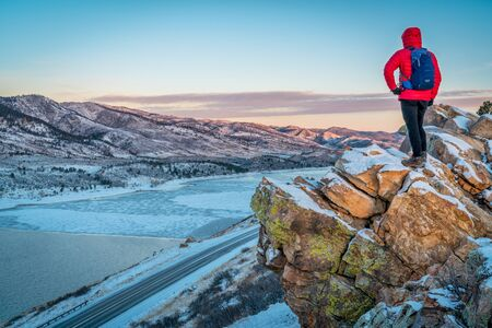 horsetooth reservoir: male hiker  contemplating winter  sunrise over frozen Horsetooth Reservoir  at Rocky Mountains foothills near Fort Collins, Colorado Stock Photo