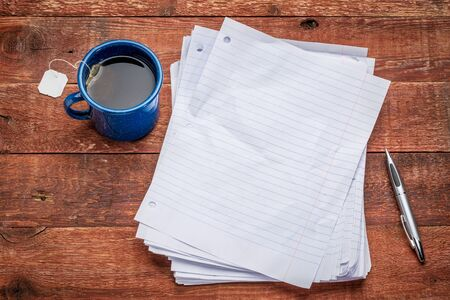 a stack of blank paper sheets on a rustic wood table with a metal mug of tea
