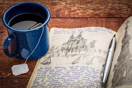 reis- of expeditie tijdschrift - handschrift en tekenen in potlood in een notebook tegen rustieke picknick tafel met een kopje thee Stockfoto