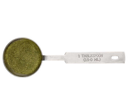wheatgrass powder in a metal measuring tablespoon isolated on white Reklamní fotografie