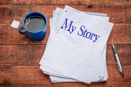 my story handwriting -  stack of paper sheets on a rustic wood table with a metal mug of tea