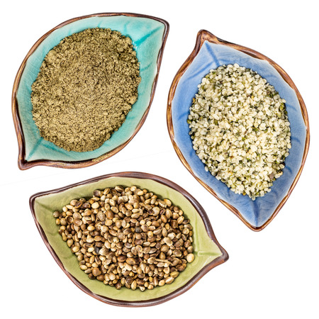 hemp hemp seed: a set of hemp seeds, hearts and  protein powder, top view of isolated leaf shaped ceramic bowls