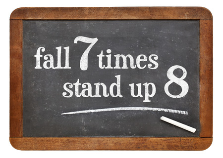 proverb: Fall seven times, stand up eight. Japanese proverb on vintage blackboard. Determination concept.