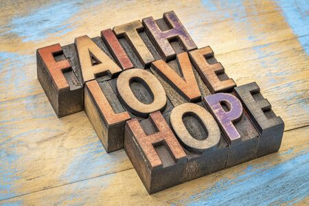 letterpress words: faith, love and hope - words in vintage letterpress wood type stained by color inks against painted wood Stock Photo