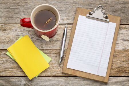blank spaces: blank paper on clipboard  with a pen, tea and sticky notes against rust wood table- office concept