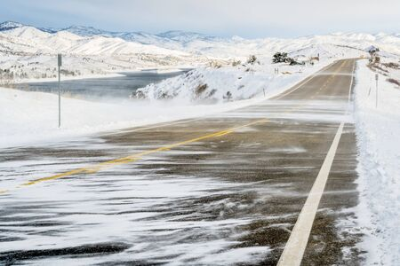 horsetooth reservoir: snow blowing wind over a road at foothills in northern Colorado near Fort Collins Stock Photo