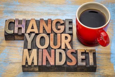 inspiracion: Cambiar su mentalidad - texto de motivación en la tipografía de época de madera tipo bloques de impresión manchados por las tintas de color con una taza de café