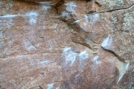 crack climb: sandstone climbing wall with white chalk marks and lichen