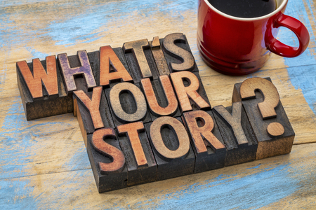 story: what is you story question - text in vintage letterpress wood type printing blocks with a cup of coffee