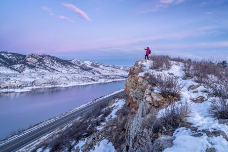 horsetooth reservoir: hiking Colorado before sunrise - male hiker on cliff above Horsetooth Reservoir in winter scenery