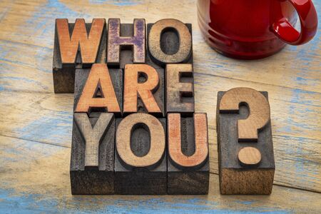 identities: Who are you question in vintage letterpress wood type printing blocks with a cup of coffee