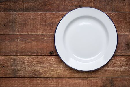 empty white metal enamel plate against rustic wood with a copy space