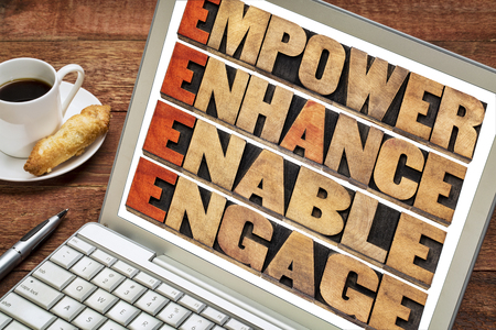 letterpress words: empower, enhance, enable and engage - motivational leadership and business concept - a collage of isolated words in letterpress wood type stained by red ink on a laptop with a cup of coffee