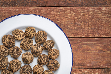 black walnuts on white metal enamel plate against rustic wood, top view with a copy space