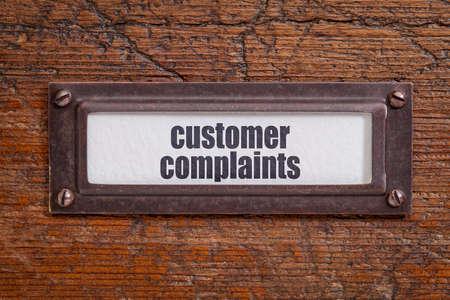 customer complaints  tag - file cabinet label, bronze holder against grunge and scratched wood