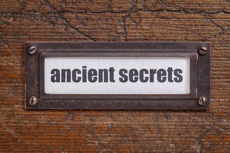metal tips: ancient secrets  tag - file cabinet label, bronze holder against grunge and scratched wood -internet publishing concept