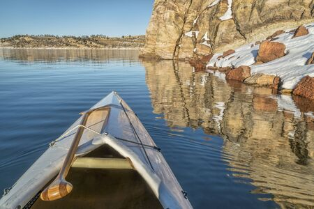 horsetooth reservoir: canoe bow with a wooden paddle on a mountain lake with sandstone cliff - Horsetooth Reservoir in Fort Collins, Colorado
