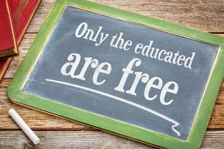 educated: Only the educated are free - inspirational message on a slate blackboard with a white chalk and a stack of books against rustic wooden table Stock Photo