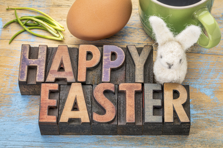 Happy Easter - greeting card, text in letterpress wood type printing blocks stained by color inks with an egg,woolen bunny and green chives 스톡 콘텐츠