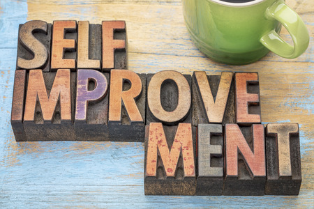 self improvement: self improvement  - word abstract in letterpress wood type printing blocks stained by color inks with a cup of coffee