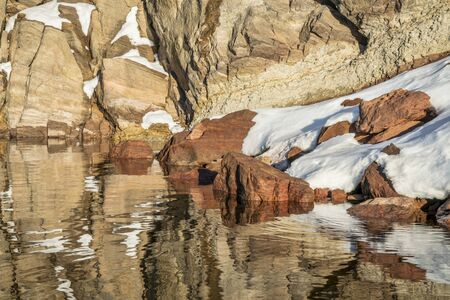 sandstone cliff, snow and water reflections - winter landscape from northern Colorado
