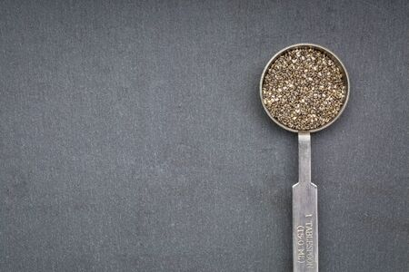 chia seed: chia seed on metal measuring tablespoon against slate sone with a copy space