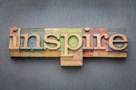 inspireren woord in boekdruk hout soort afdrukken blokken gekleurd door kleur inkt tegen leisteen achtergrond