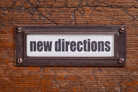 new direction: new directions   tag - file cabinet label, bronze holder against grunge and scratched wood