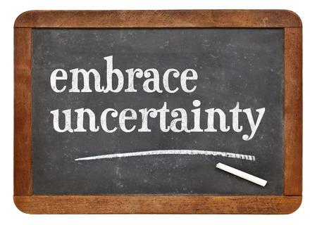 uncertainty: embrace uncertainty sign - white chalk text on a vintage slate blackboard