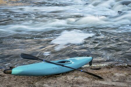 south platte river: blue plastic white water kayak with a paddle on a river shore with a rapid in background