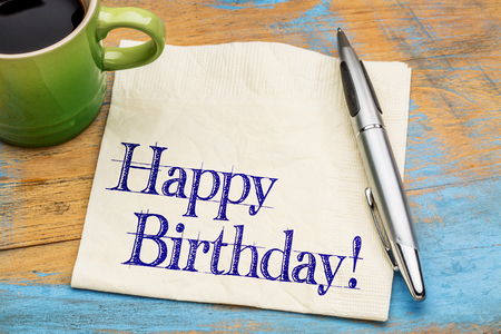 happy birthday text: Happy Birthday greeting - handwriting on a napkin with a cup of coffee