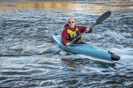 south platte river: senior male paddling a whitewater kayak on a turbulent river Stock Photo