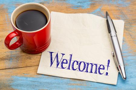 Welkom informele sign - handschrift op een servet met een kopje koffie