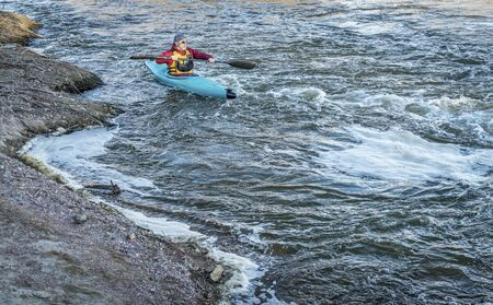upstream: male kayaker is paddling upstream of turbulent river with a fast flow