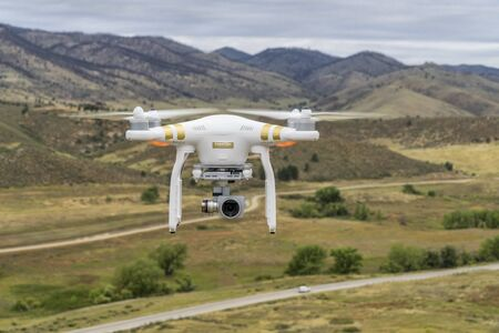 fort collins: FORT COLLINS, CO, USA, SEPTEMBER 11, 2015:  Radio controlled Phantom 3 quadcopter drone is flying with a camera over foothills of Rocky Mountains. Editorial