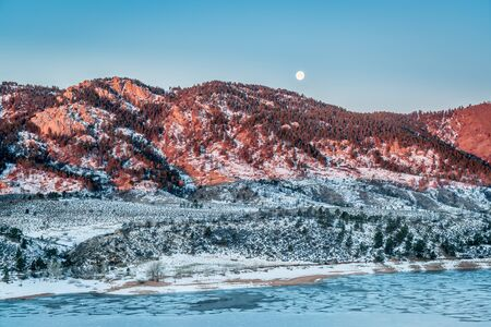 horsetooth rock: Moon setting over Arhturs Rock lit by sunrise with Horsetooth Reservoir covered by ice, Fort Collins, Colorado Stock Photo