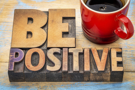 reminder: be positive banner in vintage letterpress wood type blocks stained by color inks with a cup of coffee