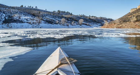horsetooth reservoir: winter canoe paddling - boat bow and partially frozen lake - Horsetooth Reservoir near Fort Collins in Colorado
