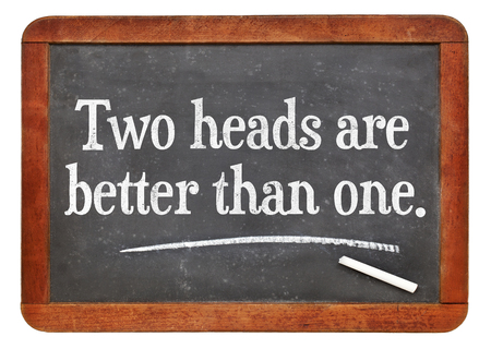 white chalk: Two heads are better than one proverb - white chalk text on a vintage slate blackboard