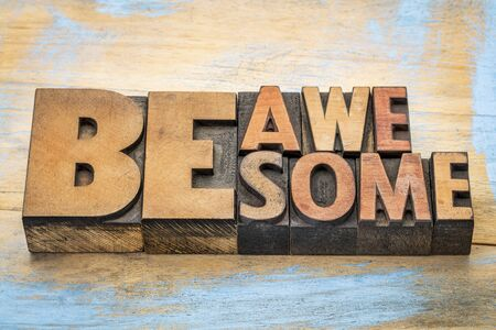 letterpress words: be awesome words in vintage letterpress wood type blocks against grunge painted wood Stock Photo