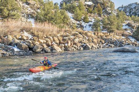 kayaker: senior kayaker in a whitewater kayak paddling upstream - Arkansas River, Colorado in winter scenery