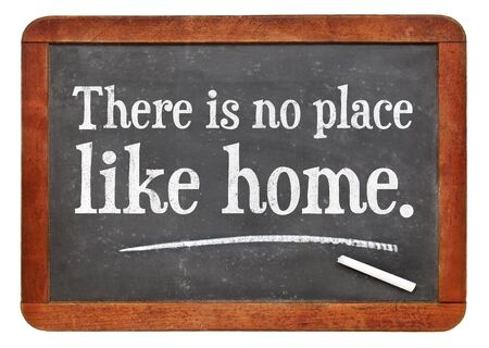 white chalk: There is no place like home proverb white chalk text on a vintage slate blackboard Stock Photo