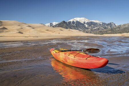 cristo: whitewater kayak in shallow waters of Medano Creek with Great Sand Dunes and Sangre de Cristo Mountains in background