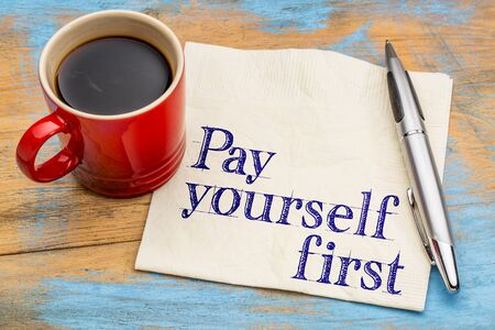 financial advice: pay yourself first financial advice - handwriting on a napkin with cup of coffee
