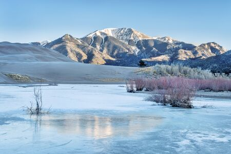frozen creek: Sunrise over frozen Medano Creek with Sangre De Cristo Mountains in background, Great Sand Dunes National Park, Colorado