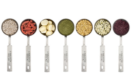 superfood abstract - white chia seeds, goji berry,macadamia nuts, barley grass powder, golden flax seeds, hemp seeds and acai berry powder - top view of  metal measuring tablespoons isolated on white
