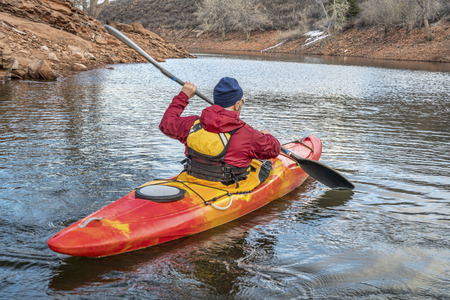 paddler: paddling colorful kayak on a calm river or lake  - recreation concept
