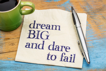 Dream big and dare to fail - motivational phrase on a napkin with a cup of coffee