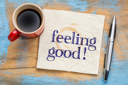 positive feelings: Feeling good handwriting on a napkin with a cup of coffee
